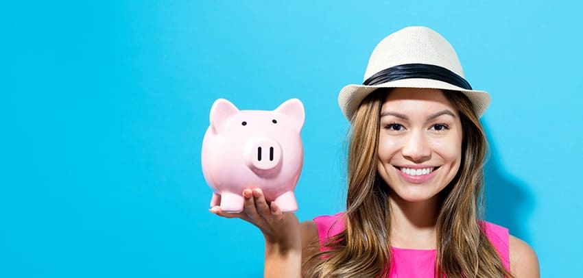 Trendy hipster girl holds a piggy bank