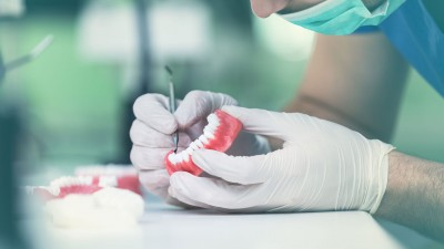 A detailed hand molds a denture for a patient