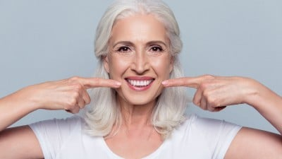 mature woman showing off her wide, happy smile after full mouth reconstruction