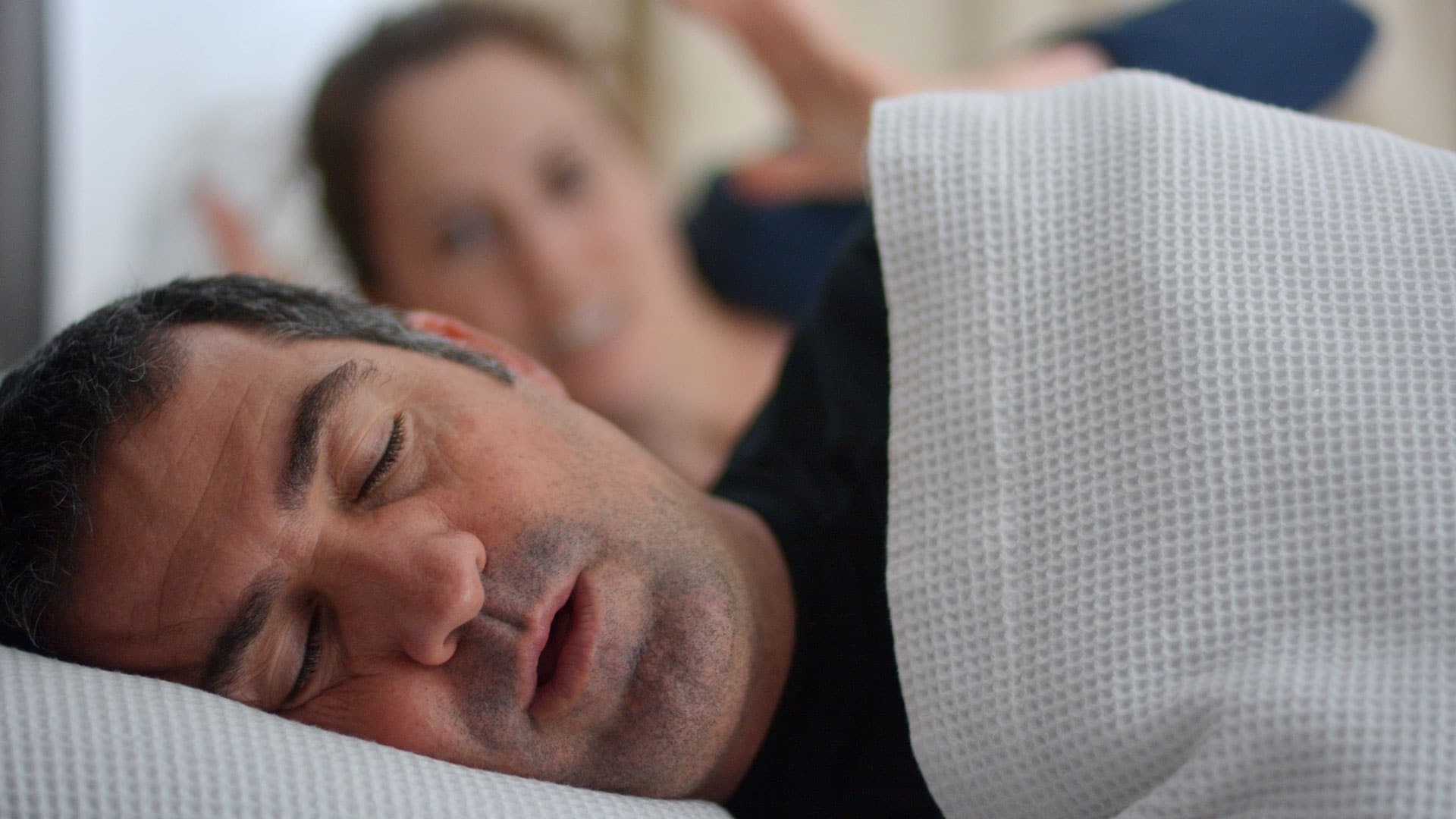 Man laying on his side snores while his wife looks on in anger