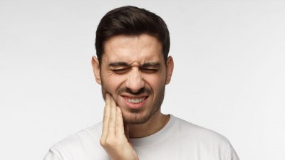 man holds his jaw in pain, experiencing TMJ symptoms