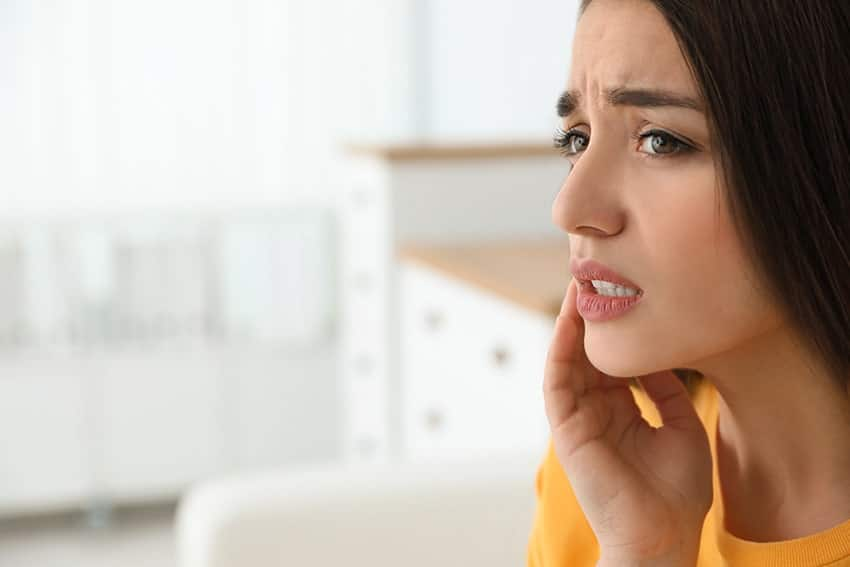attractive woman in yellow shirt presses her hand against her mouth in pain