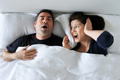 Couple sleeping with man snoring.