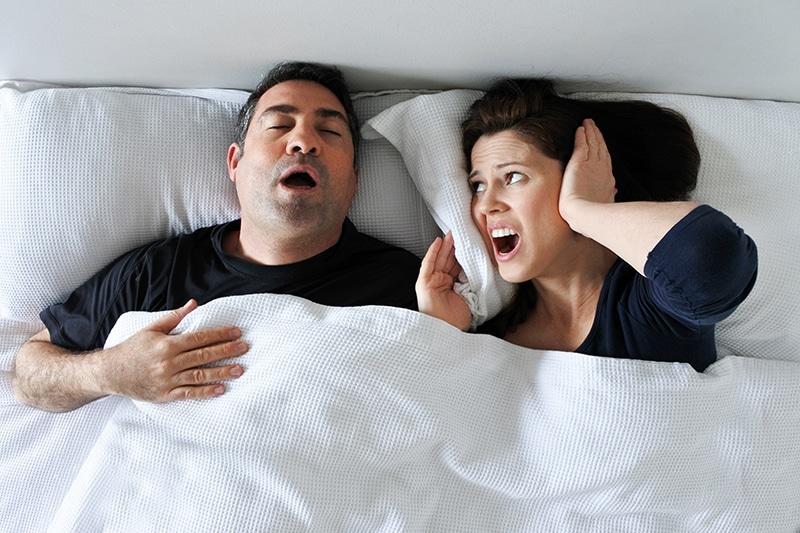 Couple sleeping with man snoring.