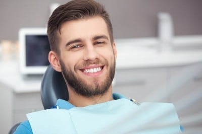 A smiling man in a dental chair.