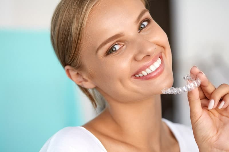 Woman holding an invisalign aligner tray.