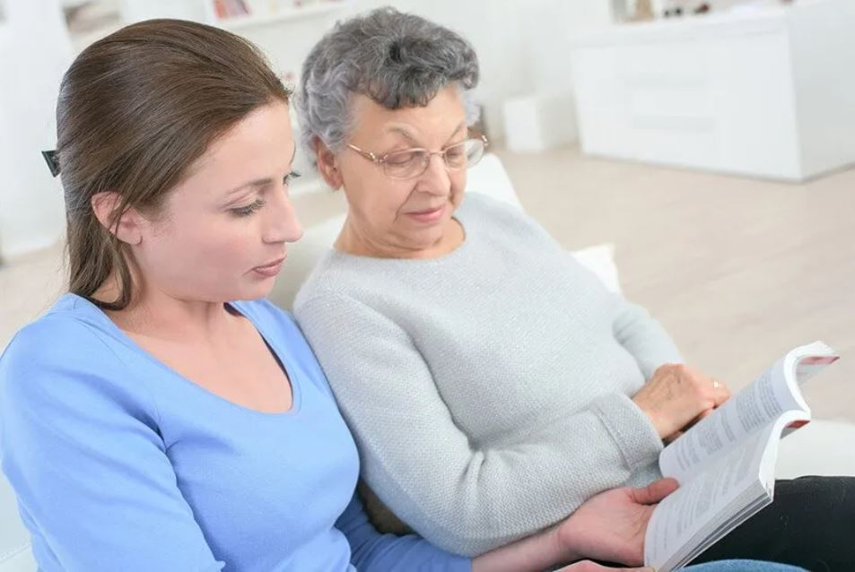 Young woman reads to her grandmother with Alzheimer's