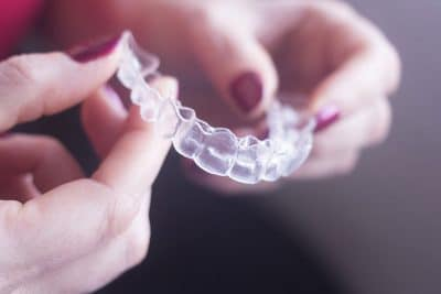female hands holding Invisalign clear braces