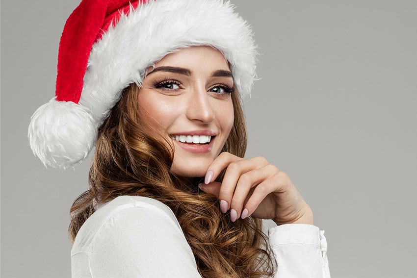 Beautiful woman in a Santa hat showing off her amazing smile