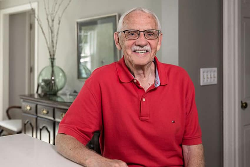 senior man in red polo shirt relaxes in his kitchen
