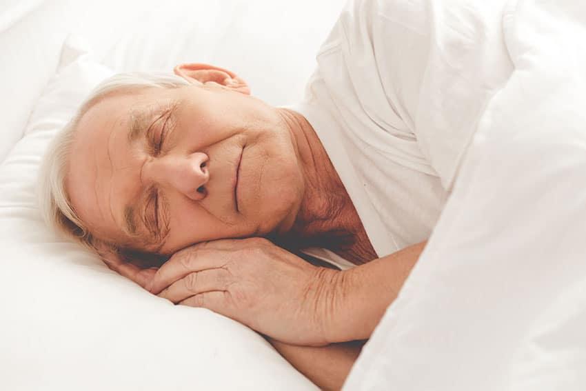 elderly man sleeping peacefully in bed