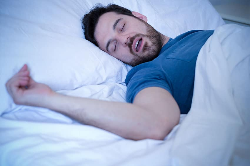 man snoring while laying in bed