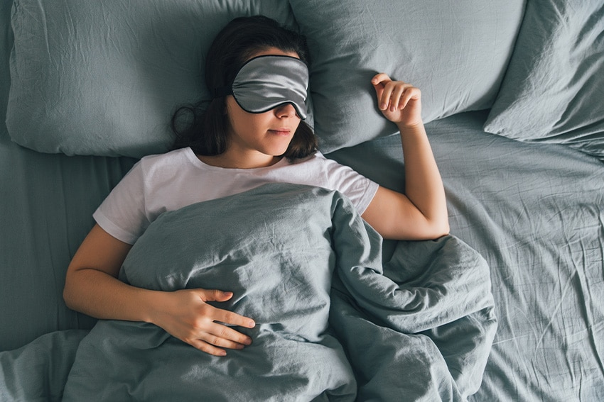 woman with mask over eyes sleeping soundly.
